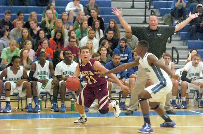 Oakton guard Thomas Tribble drives against South Lakes guard Brandon Kamga in front of South Lakes Head Coach Andrew Duggan and the Seahawks' bench on Nov. 29.