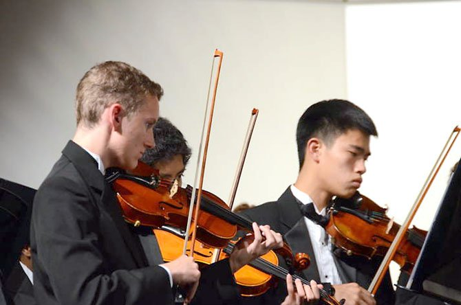 Langley High School Orchestra violinists, from left: Tim Kostelancik, Kurt Tran (hidden), Quan Pham.