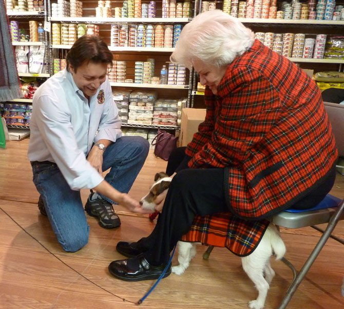 Old Town School for Dogs owner Carlos Mejias visits with Vola Lawson and her Jack Russell terrier Willie prior to a Dec. 2 photo shoot to benefit the Animal Welfare League of Alexandria.