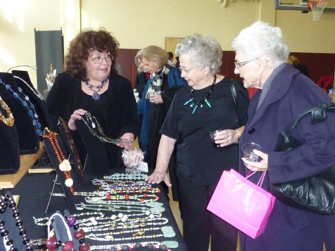 Artisan Cathy Harl, left, showcases her latest works to shoppers Patricia Harl and Pat Libhart at last year's Holiday Market to benefit the city's women's programs.