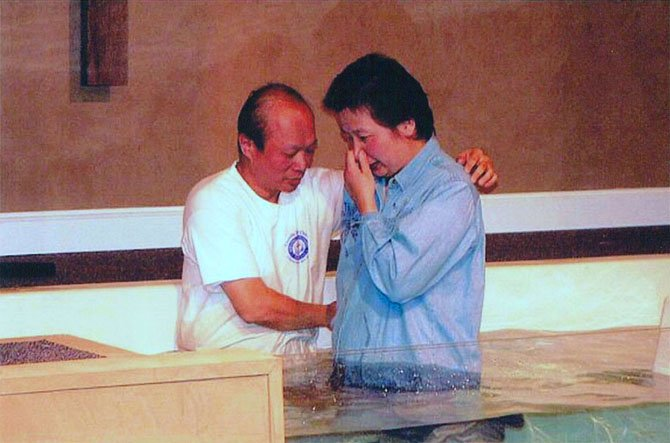 Pastor Isaac Huang of Chantilly Bible Church, who emigrated from Taiwan in 1982, baptizes a fellow Chinese immigrant.