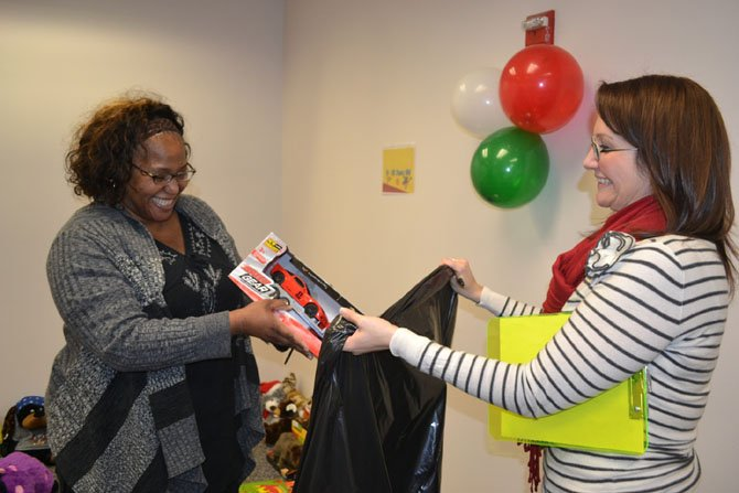 Education coordinator Krista Sofonia (right) helps an inmate's family member as she selects gifts.
