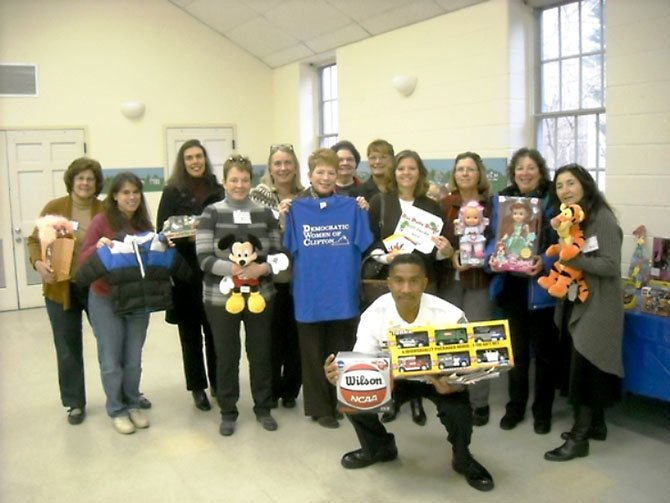 At its Nov. 18 general meeting, the Democratic Women of Clifton members collected toys, gift cards to Target, Old Navy and grocery stores, and donations to purchase winter coats for children. Members of the DWC gather around Captain Will Bailey of the Fairfax County Fire and Rescue Department (front), who holds a donated basketball and toy trucks. Lisa Whetzel, executive director of Our Daily Bread, stands directly behind him.