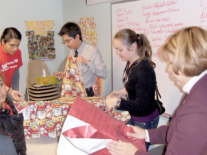 Bank of America volunteers wrapping presents are (from left) Amilcar Ferrufino, Mauricio Matallana, Carmen Berdea and Maria Sorto.