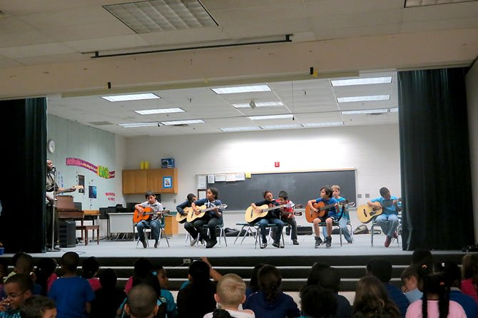 A group of guitarists take the stage to show their musical skills as the crowd sings along.