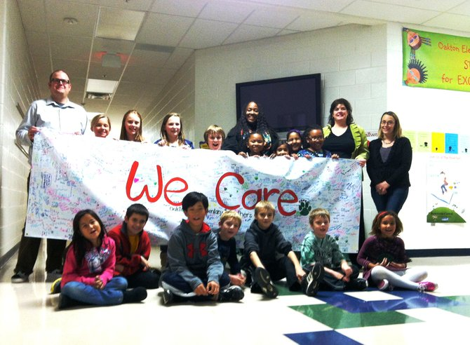 "From left—OES Librarian Kevin Hjelm, PTA president Alysia Dempsey, and PTA volunteers Tammy DiBlasi and Mary Pat Julian help students hold up the 10-foot ""We Care"" banner displayed during the school's Book Fair last week."