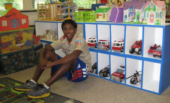 Suddy Sriram of Troop 869 sits in front of the shelves, which he built as part of his Eagle Scout Project in the summer of 2012.