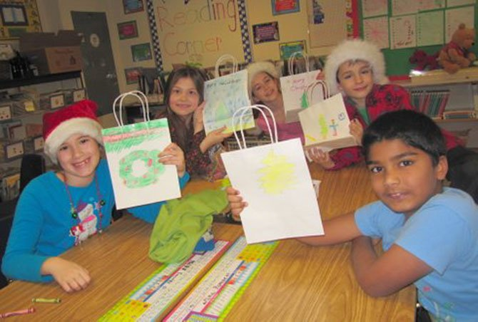 Churchill Road second graders in Cheryl Bamdad's class are proud of the gift bags they decorated for students at their buddy school, Dogwood Elementary. From left are Emma Cox, Ana Snyder, Lucy Spence, Simonas Pavilionis and Joshua John.