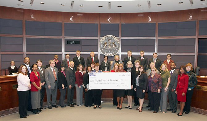 Kelly Brinkley (holding the check on the right), the COO of United Way of the National Capital Area, awards the Community Impact Grant check at the first Fairfax County Board of Supervisors meeting of the year. Surrounding Brinkley are representatives from all the Fairfax/Falls Church grantees.