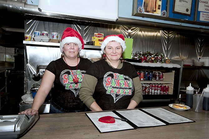 "Wait staff and cooks, from left, Barbara ""Barbie"" Gollick and Angie Brosen, display one of the several holiday t-shirts for the 29 Diner and their Santa hats."