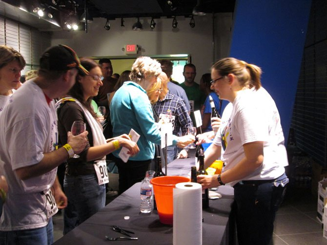 "At the wine station sponsored by King Street Blues, participants were offered samples of five different wines, including selections from Kim Crawford (pinot grigio and chardonnay), Drylands Estate, Nobilio and Thorn Clark ""Terre Barossa."" Wine pourers watched carefully to ensure that sample tickets were deposited into yellow plastic buckets before serving up samples of wine."