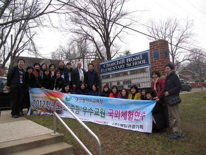 Korean teachers from the Daegu Metropolitan Office of Education posed with Principal Donald Hutzel outside Churchill Road Elementary School at the conclusion of their visit.