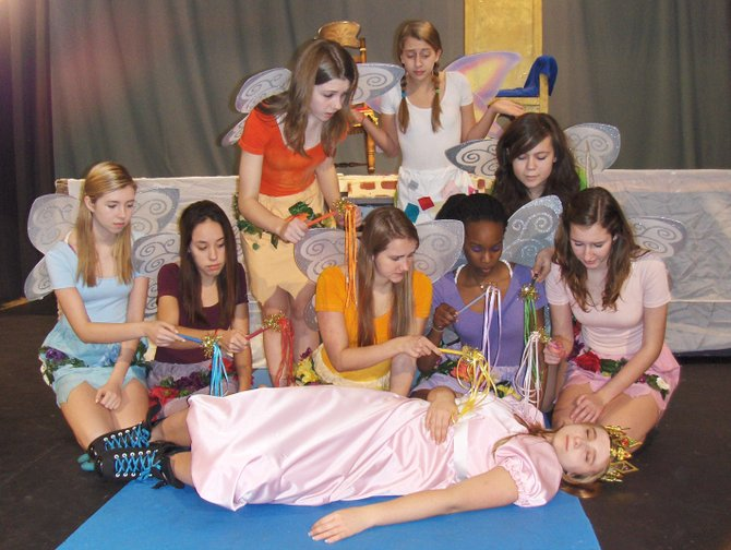 The fairies try to wake Sleeping Beauty (Annie Tkacik, wearing roller skates) in Robinson's children's show.
