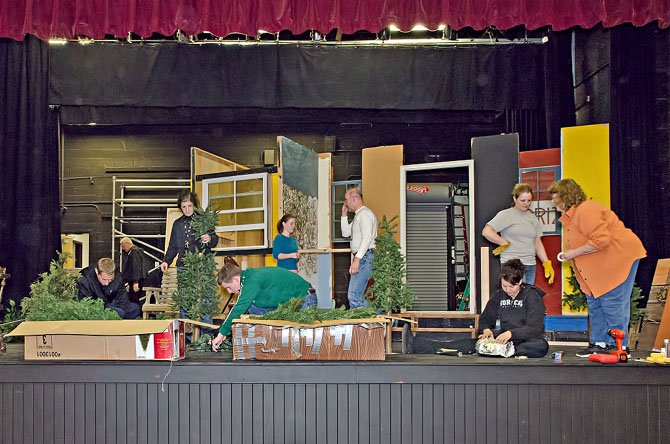 Cast and crew work together to build the set for the Vienna Theatre Companys winter product of Proposals, opening at the Vienna Community Center on January 25.  Director Suzanne Maloney is on right; her father, Norman Chaudet, founded the Vienna Theatre Company in 1974.