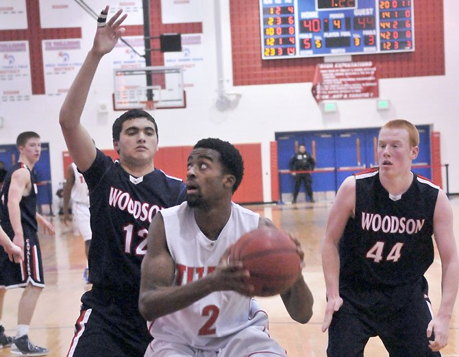 Woodson's Alex Boock (12) defends T.C. Williams' Landon Moss as Woodson's Peter Murray (44) is nearby on Tuesday night at T.C. Williams High School.
