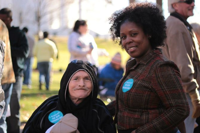 An individual with a disability and his caregiver wearing 'I Support The New Virginia Way' stickers at the Martin Luther King Day Rally in Richmond.