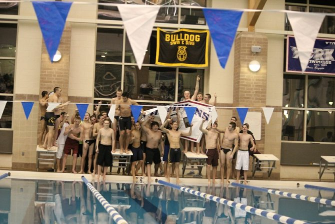 The Oakton High boys' team poses with the Concorde District banner after winning the championship meet.