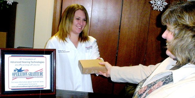 Advanced Hearing Technologies, Inc. associate Sherrie Courson accepting a care package at a local hearing lab.