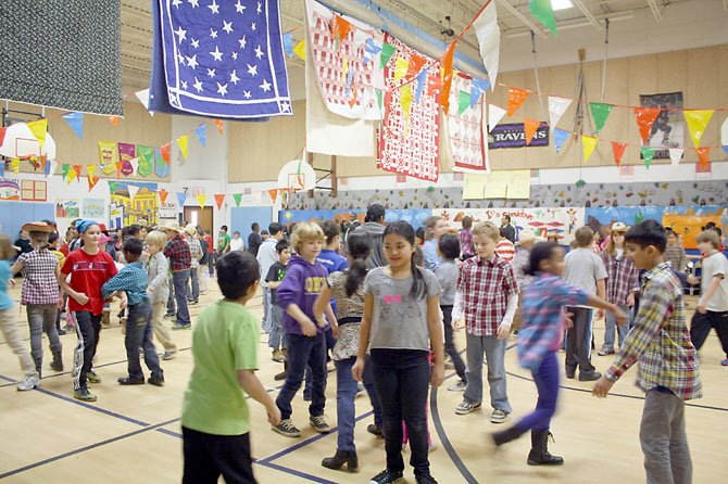 Keene Mill students square dance to the calls of Mr. Mac McCall, a professional caller at the Hoedown.