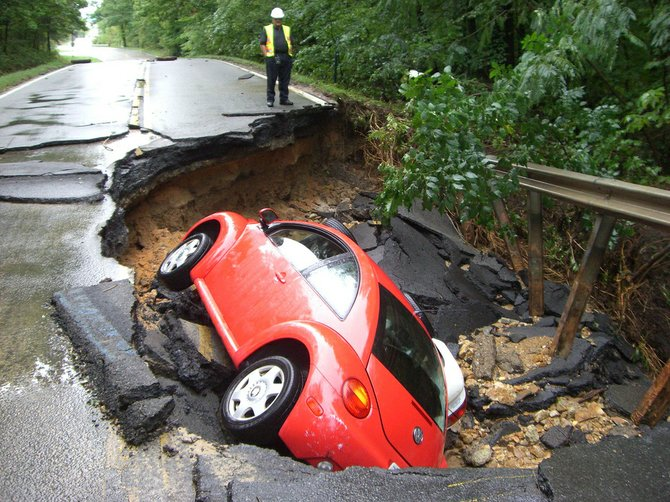 A VDOT crew member assesses damage to Lorton Road after Tropical Storm Lee in Sept. 2011, which destroyed three bridges on secondary roads, damaged pavement on dozens of roads and cost the state $10 million in transportation funds. By law, Virginia must repair damaged roads before spending money to build new ones.