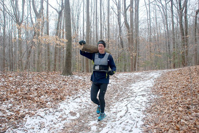 Burke resident Lance Sanson trains for the Spartan Death Race by jogging on Fountainhead Regional Park with a log over his shoulder.