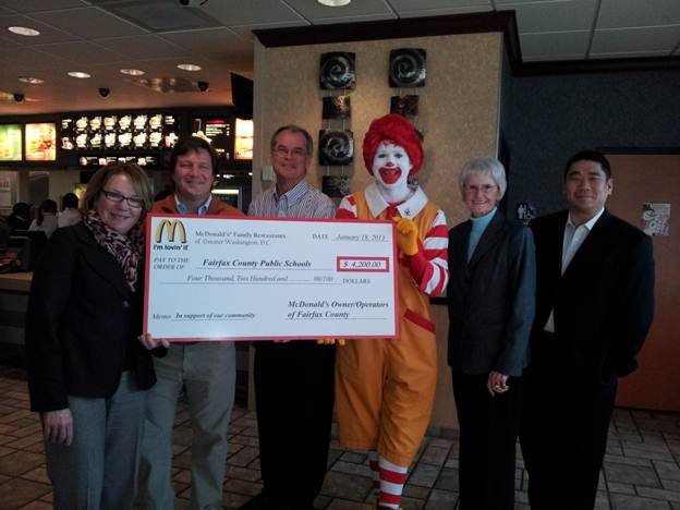 From left: Christine Donohue (Chief of Staff, FCPS), Jay Garant (coordinator, Business and Community Partnerships- FCPS), Jim Van Valkenburg (McDonald's owner/operator), Ronald McDonald, Neva Van Valkenburg (McDonald's owner/operator), Kyu Rhee (McDonald's owner/operator). The owners/operators in this picture own restaurants in Fairfax County and contributed to the total donation.