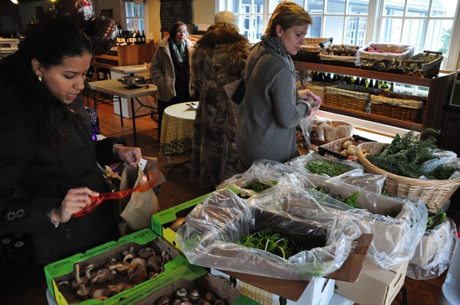 Shoppers browse a selection of greens and other produce at the Great Falls Farmer's Market Saturday, Feb. 2. The market is happening all winter long, either at its usual site, or inside Maison du Vin on days with below-freezing temperatures.