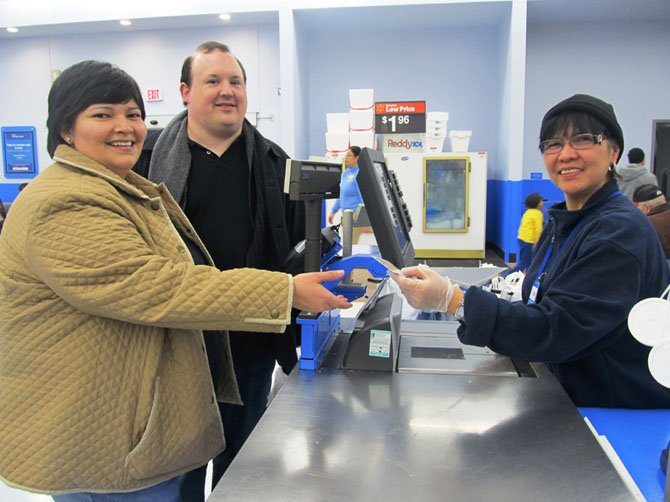 "Jonathan and Roxanne Daley of Fairfax purchase a gift card from Wal-Mart to help restock Our Daily Bread's pantry shelves during a ""Stuff the Bus"" stop on Saturday, Feb. 3, at the Fairfax Wal-Mart."
