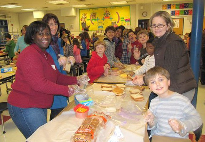 Churchill Road students and parents made sandwiches for Marthas Table, a non-profit organization which serves food to those in need. Pictured from left are Kelly Khan, Lauri Dacey, Barney Smithers, James Murray, Mariano Olsen-Fappiano, Ethan Carlisle, Jackson Khan, Laura Carlisle and Luke Carlisle.