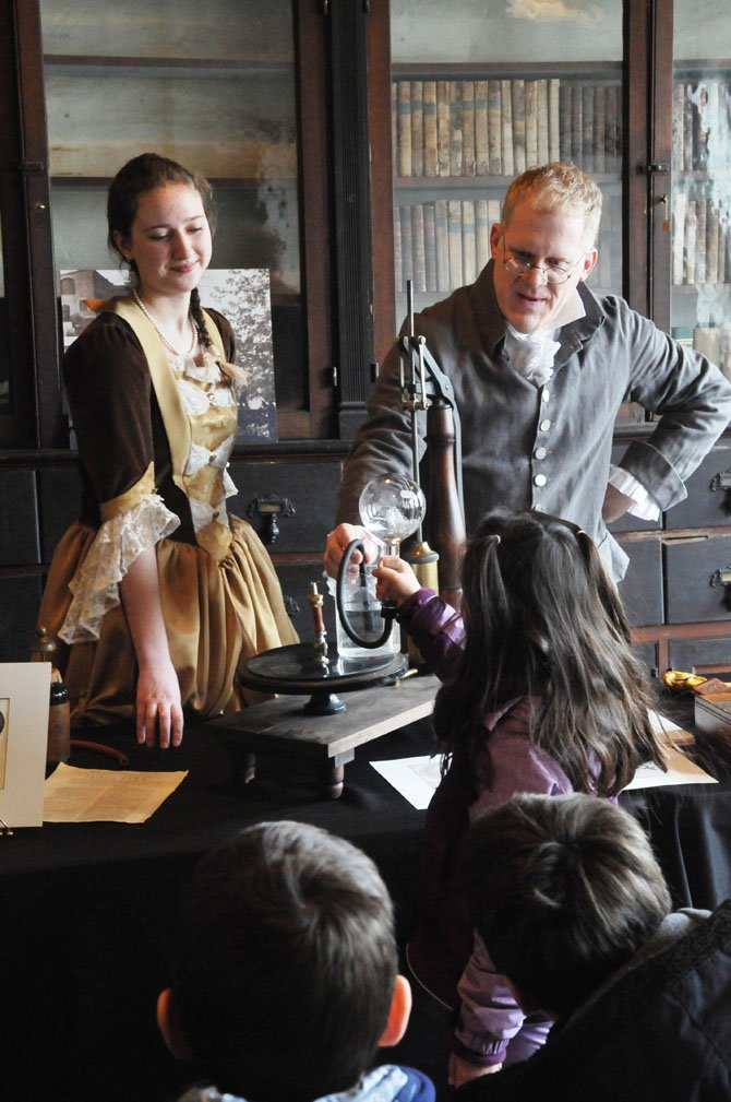 Dr. John Page (Dean Howarth) demonstrates a simple vacuum machine to a young group of students at the apothecary shop on Saturday afternoon, Feb. 2. With Howarth is Hannah Jones portraying balloonist Sophie Blanchard.