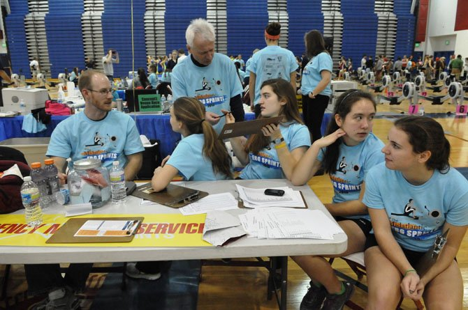Volunteer Milos Ivanis checks in with the other volunteers on the floor during the erg sprints on Saturday afternoon.