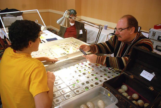 Collector-seller Joe Riggs examines a coin virtually for a young collector.