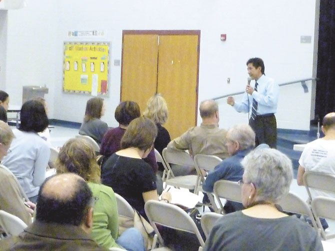 Chair of the Arlington County Board Walter Tejada answers questions from Arlington residents at Drew Community Center.