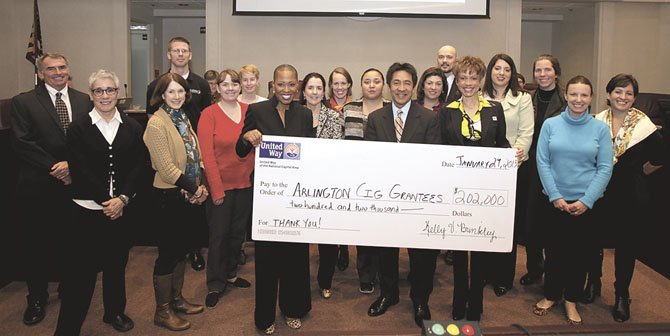 Holding the check from left is United Way NCA Chief Operating Officer Kelly Brinkley, Arlington County Board of Supervisors Chair Walter Tejada, and United Way NCA Arlington Regional Council Chair Leah Wallace. They are surrounded by the Arlington Community Impact Fund grantees.
