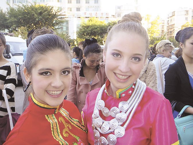 Sofia Falçao from Portugal and Molly Reiner of Potomac wear their costumes before the televised taping of the closing ceremony in China.