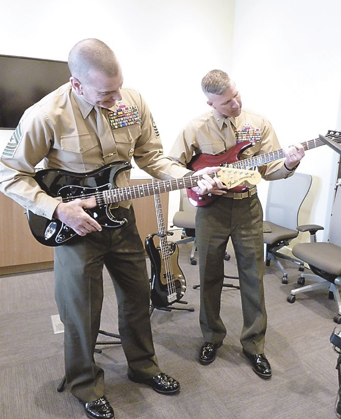 Sgt. Major Bryan Battaglia and Brigadier General Eric Smith test out guitars in the music room of the new USO facility at Fort Belvoir.