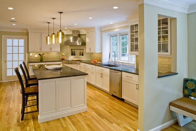 "Brent Wentworth and his team added white-painted cabinetry, glass cabinet doors, dark gray granite countertops, oak floors and pendant light fixtures that he says ""will remain functional and stylish for years to come."""