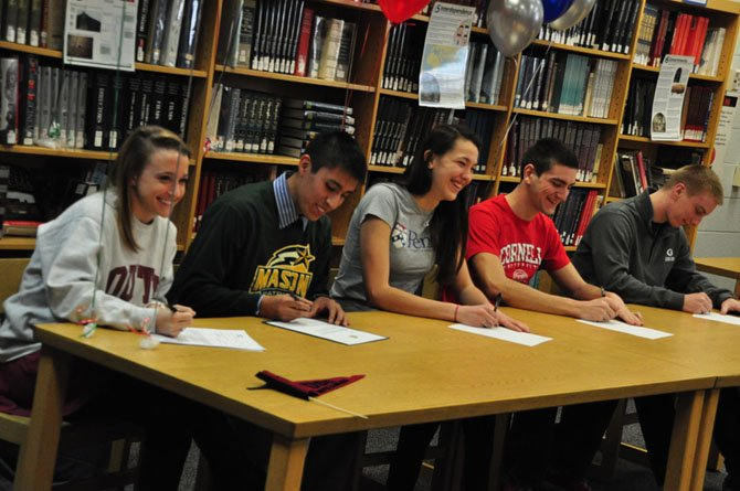 From left, McLean High School seniors Evelyn Robinson (soccer, University of South Carolina), David Galdo (soccer, George Mason University), Lexi Slotkoff (volleyball, University of Pennsylvania), Kris Hobbs (crew, Cornell University) and Robert Longwell (football, Georgetown University) sign their letters of intent to play college athletics next year.