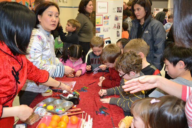 Chesterbrook Chinese teachers Peggy Leung and Beesha Hung show students how to make Chinese New Year ornaments.