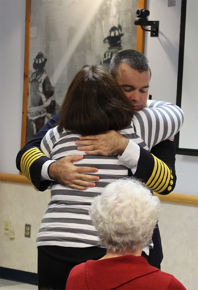 Alexandria Fire Chief Adam Thiel comforts the widow of Joshua Weissman, Rebecca Weissman.