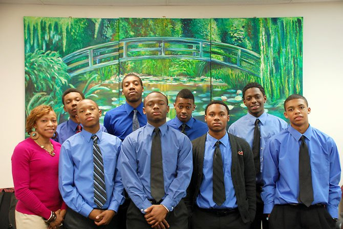 Lee social worker Marcella Fulmore is joined by PAAMAS members (bottom, from left) seniors Thomas Watson, Ashwin Pitt, Demond Richeson, sophomore Darryl Gray, (top, from left) seniors Pearson Wheatley and David Johnson, junior Daniel Williams and sophomore Jonathan Walters.