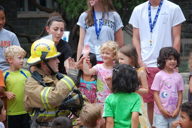 Student attending the Norwood School summer camp in Bethesda, Md., spend time with a firefighter.