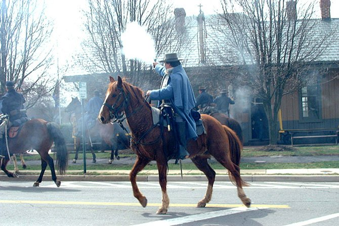 A Confederate re-enactor fires at Union soldiers during the 2001 re-enactment of Capt. John Mosby's raid on Herndon. The town will host another re-enactment of the event Saturday, March 17 at 11 a.m. and 2 p.m.