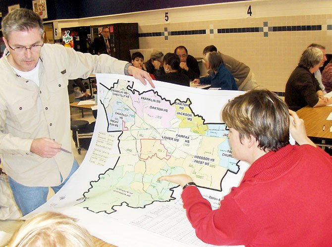 Parents Bernie Feord and Jennifer Willey examine one of the boundary-change maps.