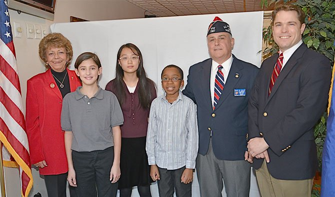 VFW Post 7327 Ladies Auxiliary President Linda Bond, Patriot's Pen Award first place winner Shane King, second place winner Sion Kim, third place winner Rishon Elliott, Post Commander Gary Kelch and Michael Collins, from Congressman Gerry Connolly's office. The winners were all sixth grade classmates from Keene Mill Elementary.