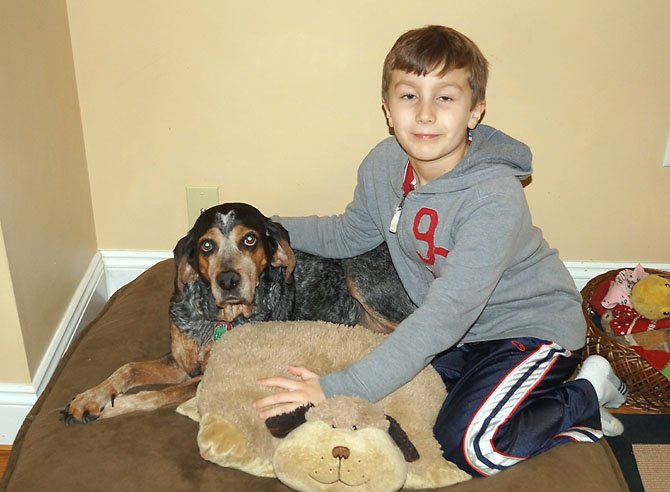 Jonathan Fernandez of Burke area cuddles and poses with Kristy, who the family adopted in July of 2007.