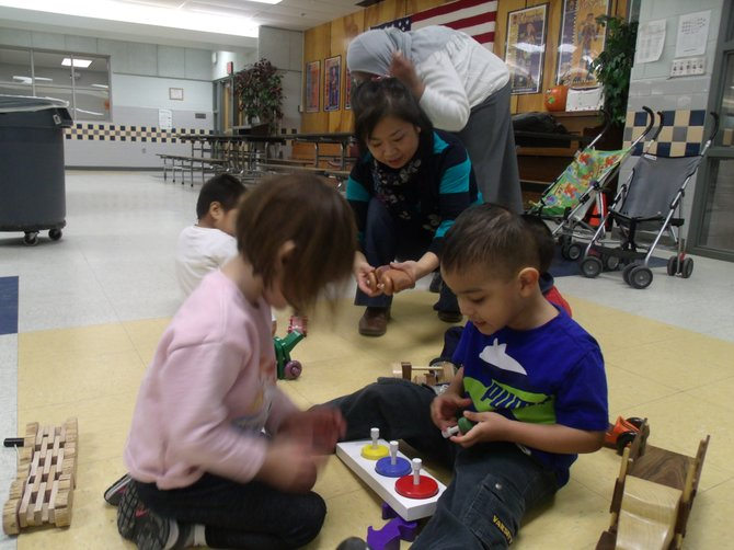 Preschool children of Forest Edge Elementary School playing with donated toys by the RCC's Good Neighbor woodworking group.