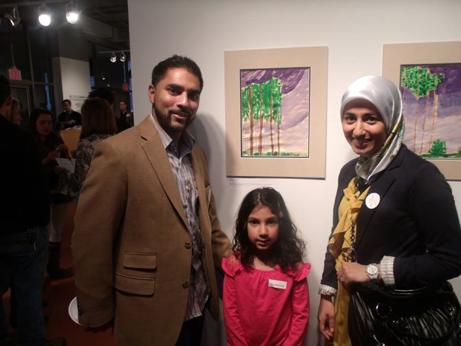 Ibrahim Moiz, father of kindergartner Asiya Moiz, a student at Al Fatih Academy, and her mom Sadaf Iqbal with Asiya's work at the exhibition.