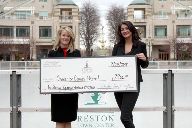 At Reston Town Center on Feb. 28, Cate Fulkerson (left), president of Reston Character Counts! Coalition, was presented with a donation check in the amount of $2,966 by Marissa Marwell (right), manager of the Reston Town Center ice skating pavilion.