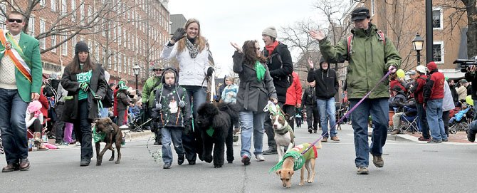 Dr. Katy Nelson and Capitol Heels co-owner Bobby Mahoney lead the dogs down King Street to start the annual parade.